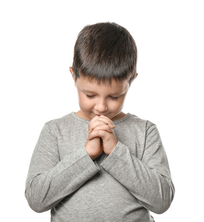 Little boy praying on white background Foto de archivo