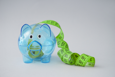 Piggy bank with measuring tape on light background. Weight loss concept Imagens