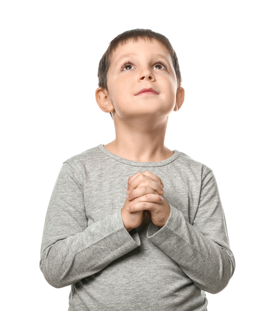 Little boy praying on white background Stock Photo
