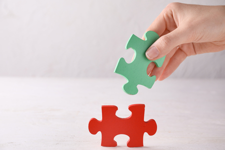 Female hand with pieces of puzzle on light background