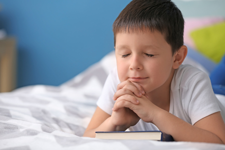 Little boy with Bible praying in bedroom