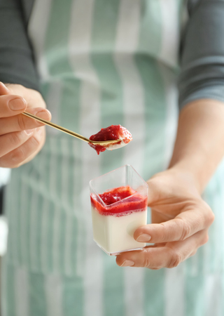 Woman eating tasty strawberry panna cotta, closeup