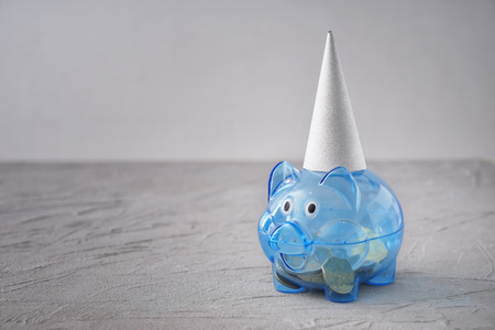 Piggy bank with party hat on table. Concept of saving money for holiday Foto de archivo - 115296490
