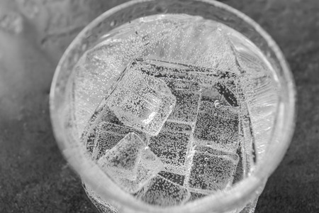 Glass of cold water on grey table, closeup