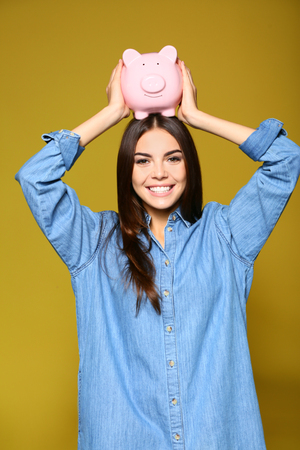 Beautiful young woman with piggy bank on color background