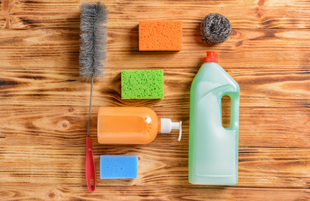 Cleaning supplies on wooden background Imagens