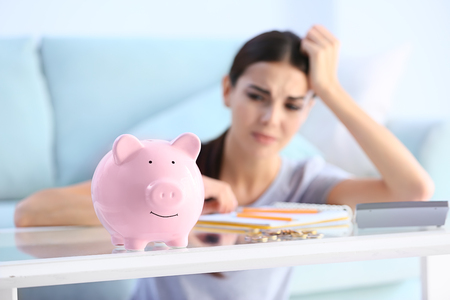 Piggy bank on table of young upset woman Stock Photo