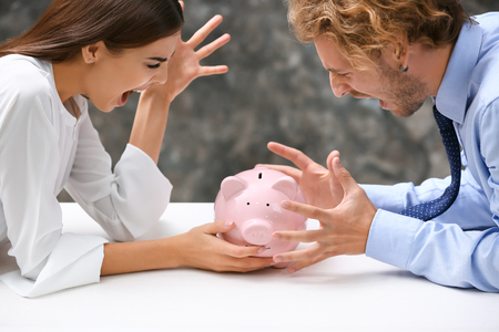 Young quarreling couple with piggy bank at table