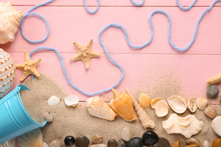 Composition with different sea shells and sand on color wooden background