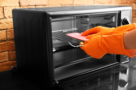 Woman cleaning electric oven with rag, closeup