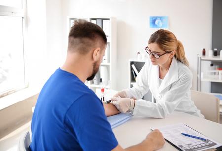 Doctora extrayendo una muestra de sangre del paciente masculino en la clínica