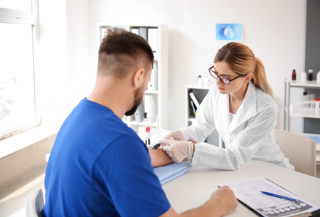 Female doctor drawing a blood sample of male patient in clinic Archivio Fotografico