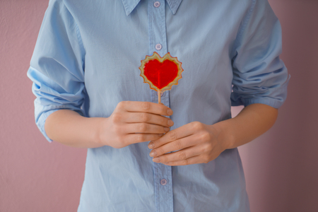 Woman holding heart shaped lollipop on color background