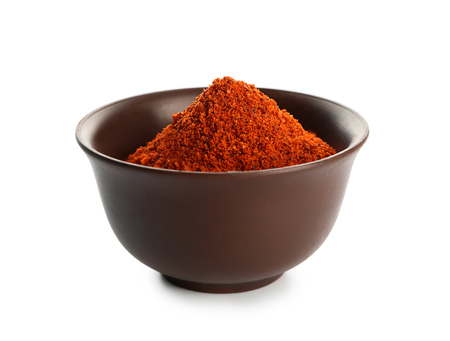 Bowl with paprika powder on white background