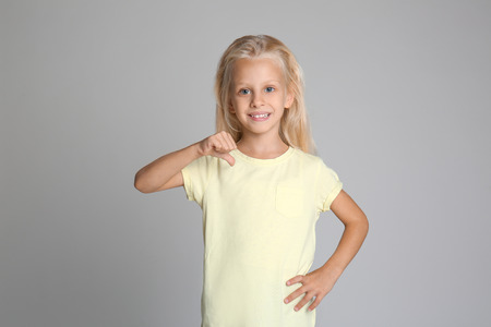 Cute little girl pointing at her t-shirt on grey background