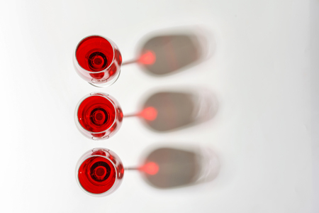 Glasses with sweet tasty wine on white background