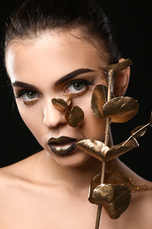 Beautiful young woman with extravagant makeup and golden eucalyptus branch on black background, closeup