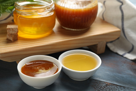 Bowls and jars of tasty honey on table, closeup