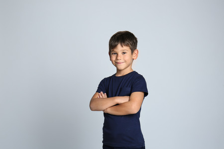 Cute little boy in t-shirt on grey background