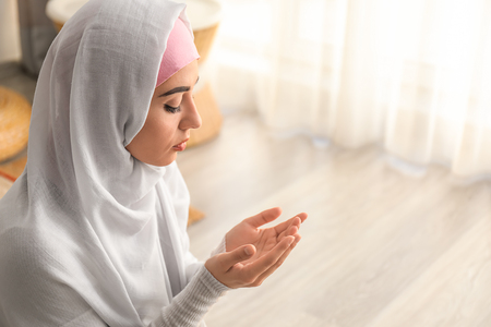 Young Muslim woman praying at home