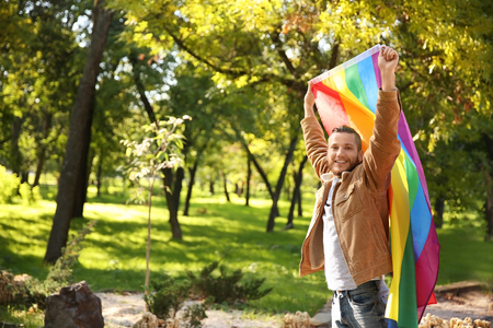 Young man with rainbow LGBT flag in park Archivio Fotografico