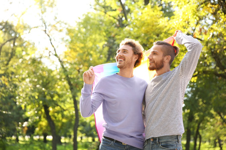 Happy gay couple with rainbow LGBT flag in park Stockfoto
