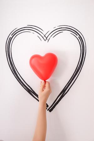 Female hand holding heart-shaped air balloon near white wall Stock fotó