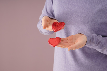 Woman holding decorative hearts on color background, closeup 写真素材