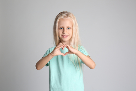 Cute little girl in t-shirt making heart with her hands on grey background