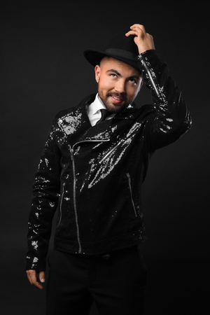 Male magician on dark background