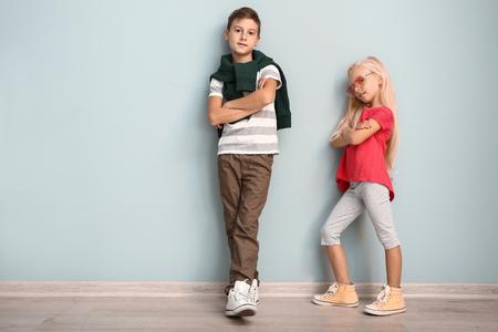 Chico y chica lindos en ropa de moda junto a la pared de color