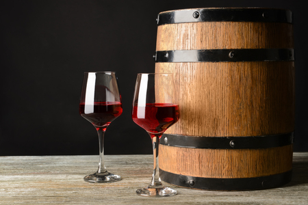 Barrel and glasses of red wine on wooden table 写真素材