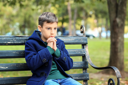 Praying little boy sitting on bench in park Фото со стока