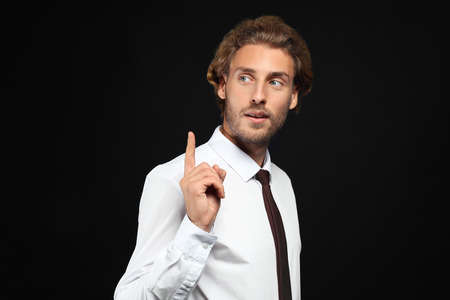 Handsome businessman with raised index finger on black background