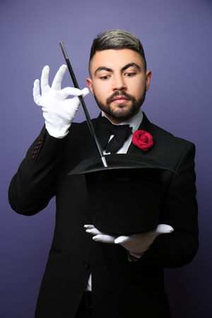 Male magician showing tricks with hat on color background
