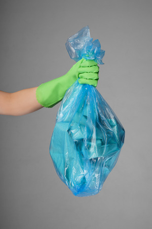 Woman holding garbage bag on grey background