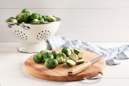 Wooden board with fresh brussels sprouts on table