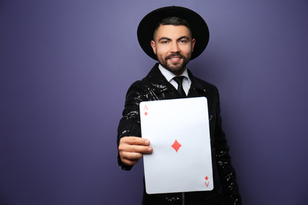 Male magician showing tricks with card on color background