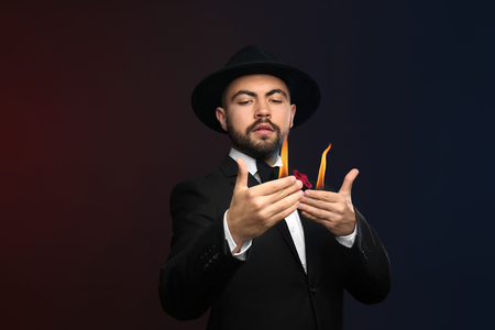 Male magician showing tricks on dark background
