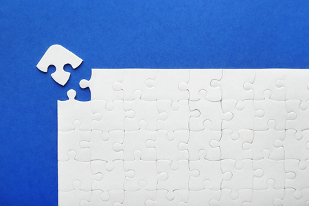 White jigsaw puzzle with piece on color background