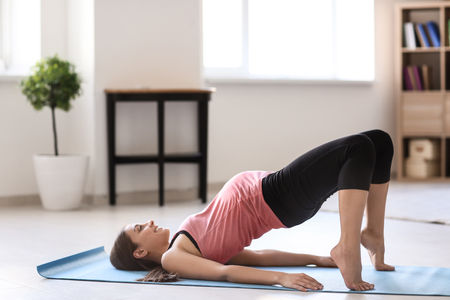 Young pregnant woman practicing yoga at home Stock fotó