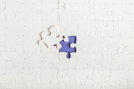 White jigsaw puzzle with piece Фото со стока