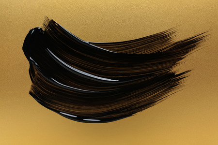 Strokes of black paint on golden background