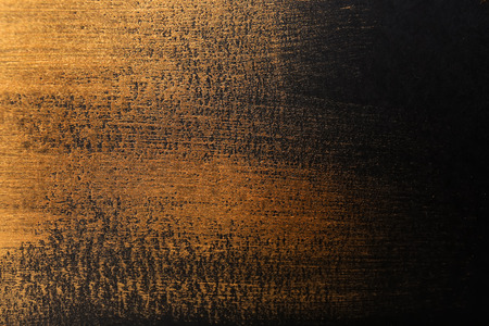 Strokes of gold paint on dark background Stock Photo