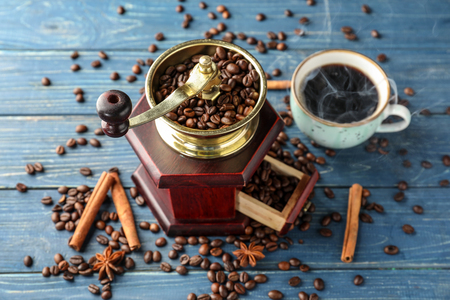 Coffee grinder and cup of hot beverage on wooden table