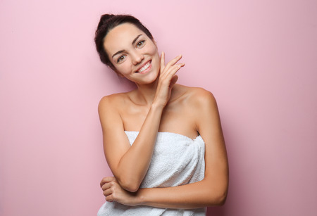 Beautiful young woman wrapped in towel on color background Stock Photo