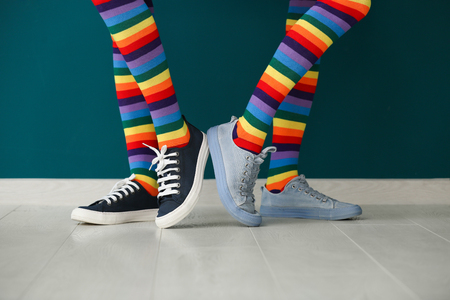 Legs of young lesbian couple in rainbow stockings standing against color wall Stock Photo