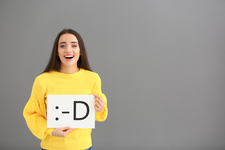 Young woman holding sheet of paper with drawn emoticon on grey background