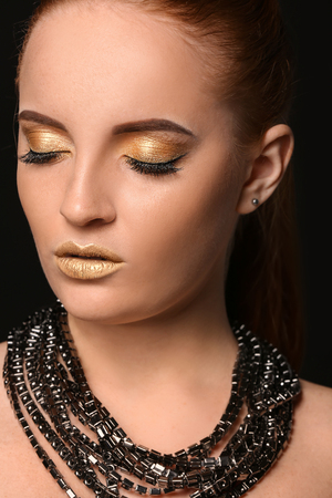 Beautiful woman with golden make up against dark background 스톡 콘텐츠