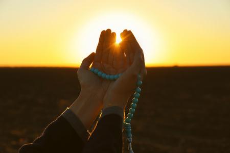 Jonge moslimvrouw bidden met kralen buitenshuis bij zonsopgang Stockfoto
